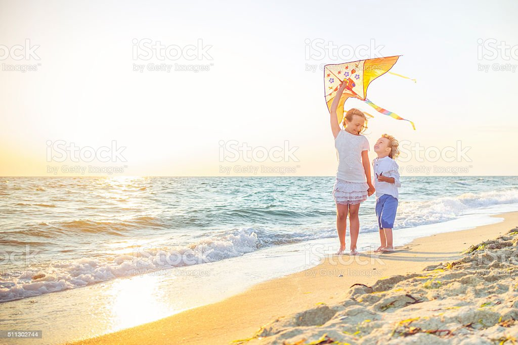 Happy kids flying kites at the beach stock photo