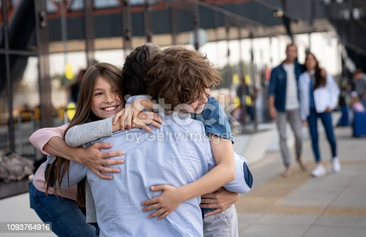 Portrait of two happy kids greeting their father at the airport after coming home from a trip – lifestyle concepts