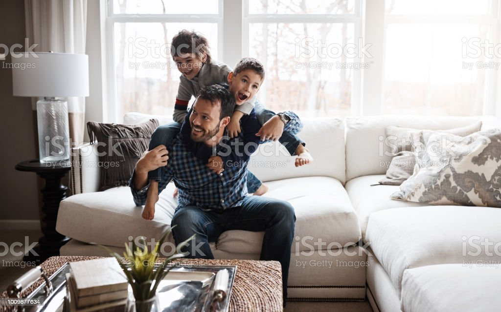 Happy kids = happy family Shot of two adorable little boys having fun with their father at home Adult Stock Photo