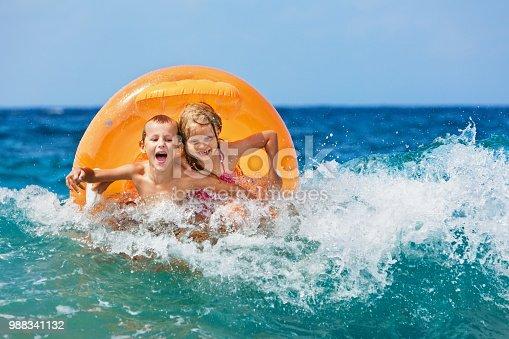 istock Happy kids have fun in sea surf on beach. 988341132