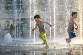 Happy kids have fun playing in city water fountain on hot summer day. Boys happy and smiling brother best friends. Ecology concept.