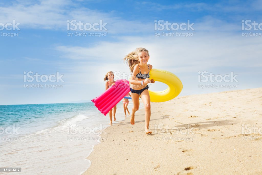 Happy kids having a race on sunny beach in summer stock photo