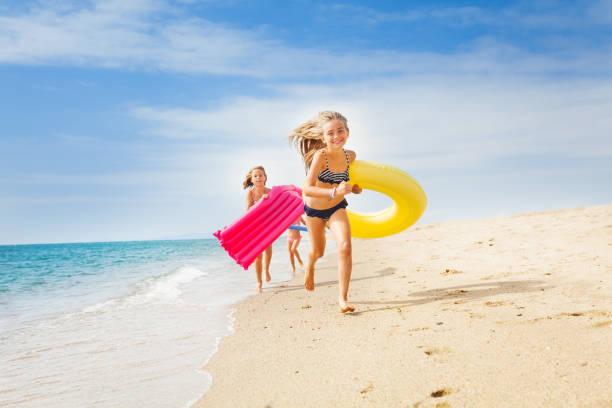 Happy kids having a race on sunny beach in summer - fotografia de stock