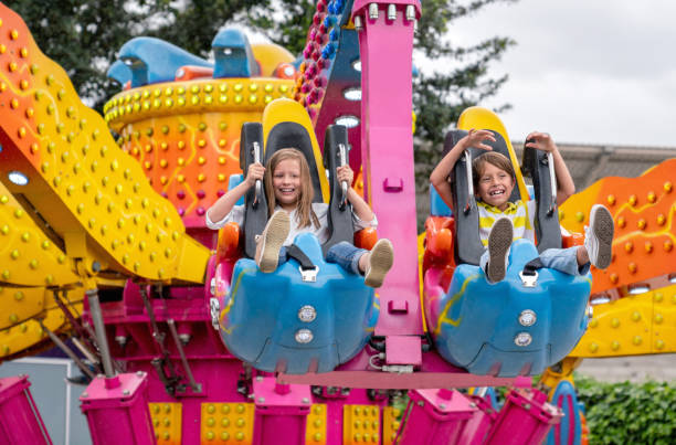 happy kids having fun in an amusement park - luna park foto e immagini stock
