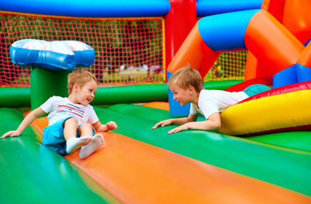 happy kids having fun on inflatable attraction playground stock photo
