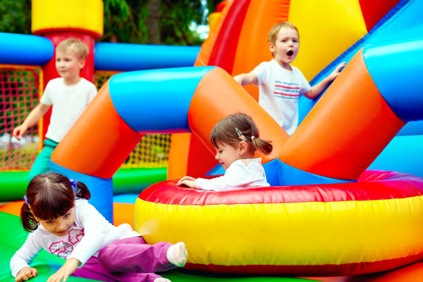 happy kids, having fun on inflatable attraction playground stock photo
