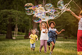 Happy kids having fun with bubbles made by street artist during spring day at the park.