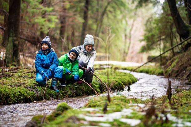 gelukkige jonge geitjes wandelaars spelen in stream met stokken - bos spelen stockfoto's en -beelden