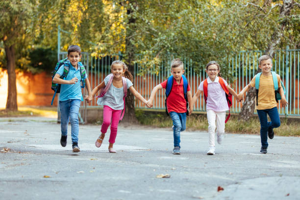 Happy kids holding hands and running joyfully after the classes stock photo