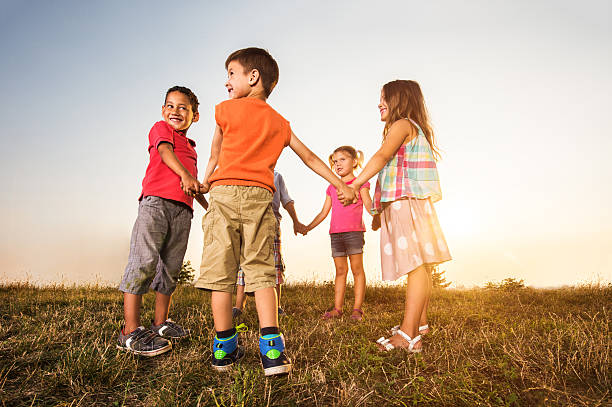 Happy kids holding hands in a circle at sunset. - Photo