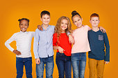 istock Happy kids hugging against orange studio background 1172150266