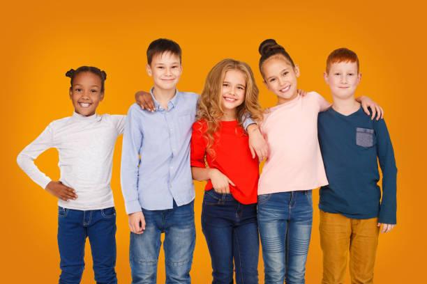 niños felices abrazando contra el fondo naranja estudio - lifestyle color background fotografías e imágenes de stock