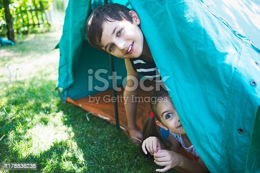 Two happy hiker kids having fun in a tent.
