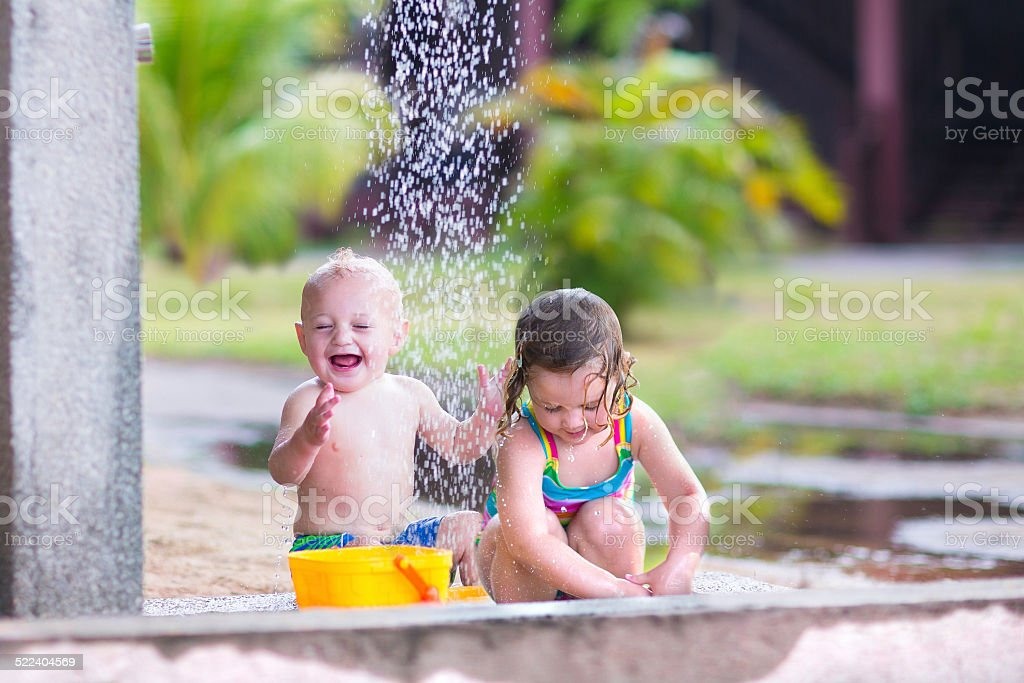 Happy kids in an outdoor shower stock photo