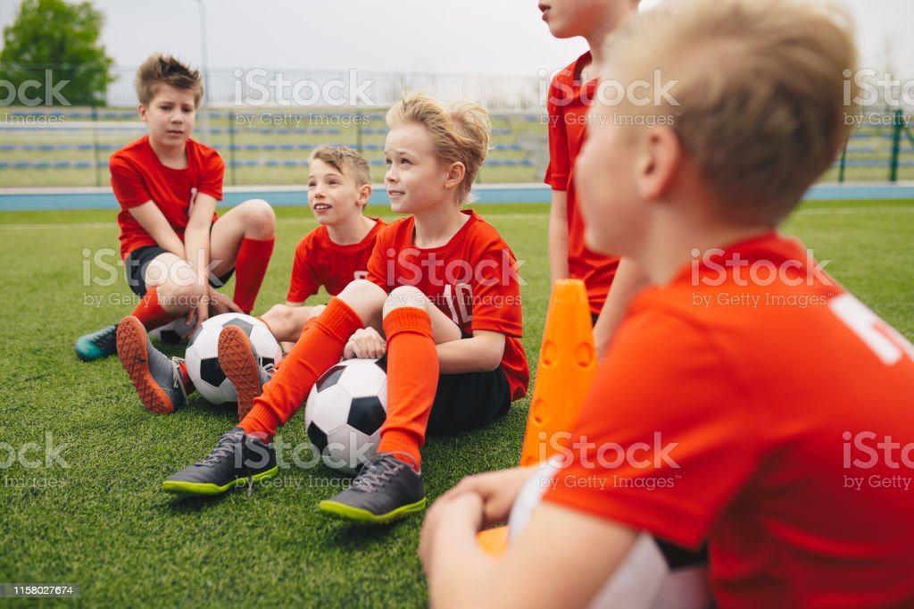 Happy kids in school sports team. Boys gathering and having fun on...