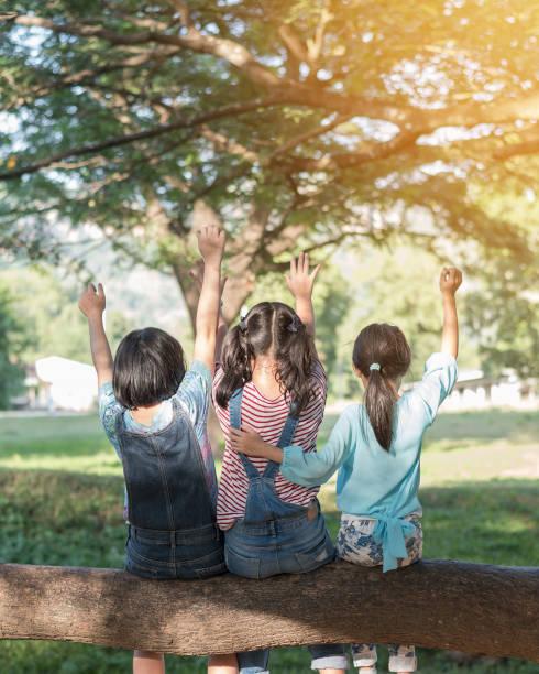 glückliche kinder in den park mit spaß sitzen unter baum schatten spielen zusammen genießen gutes gedächtnis und moment der mädchen student lebensstil mit freunden in der schule mal tag für kinder freundschaft konzept - sommerfest kindergarten stock-fotos und bilder