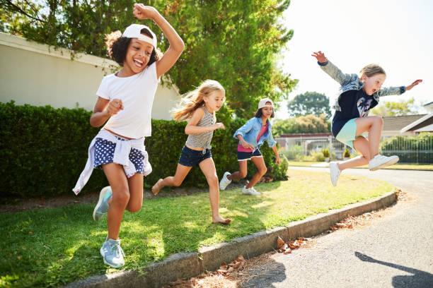 Glückliche Kinder springen und spielen draußen – Foto