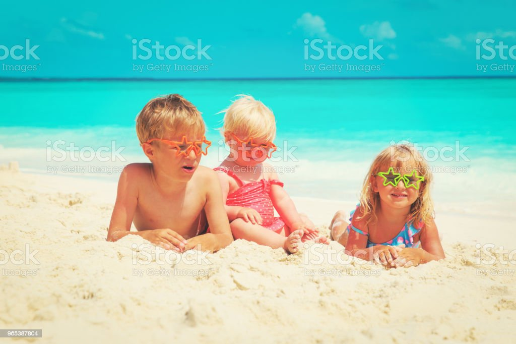happy kids- little boy and girls play with sand on beach royalty-free stock photo