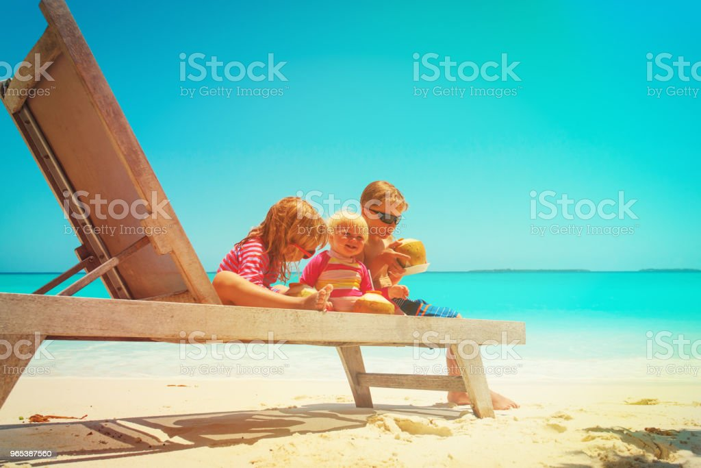 happy kids -little boy and two girls- drinking coconut on beach zbiór zdjęć royalty-free