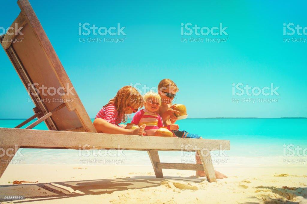 des enfants heureux - petit garçon et deux filles - noix de coco à boire sur la plage - Photo de Beauté libre de droits