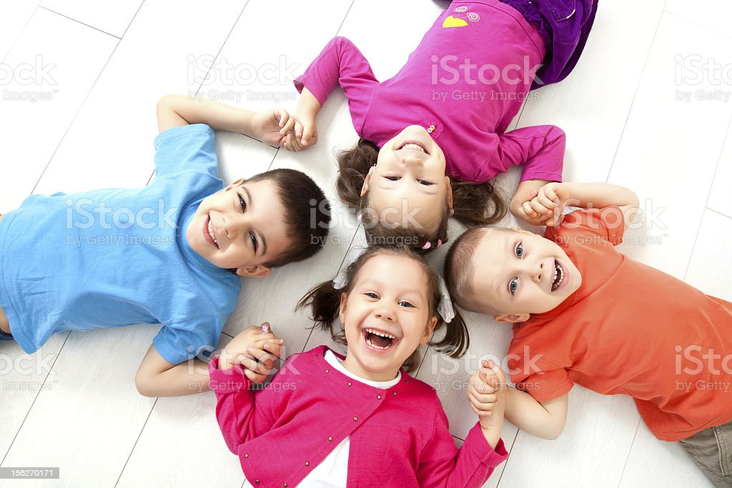 Happy kids lying face up in a circle on the floor smiling royalty-free stock photo