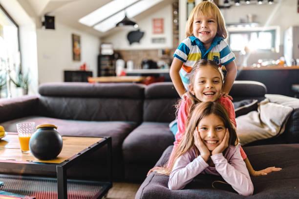 Evde kanepede insan piramidi yapan mutlu çocuklar. stok fotoğrafı