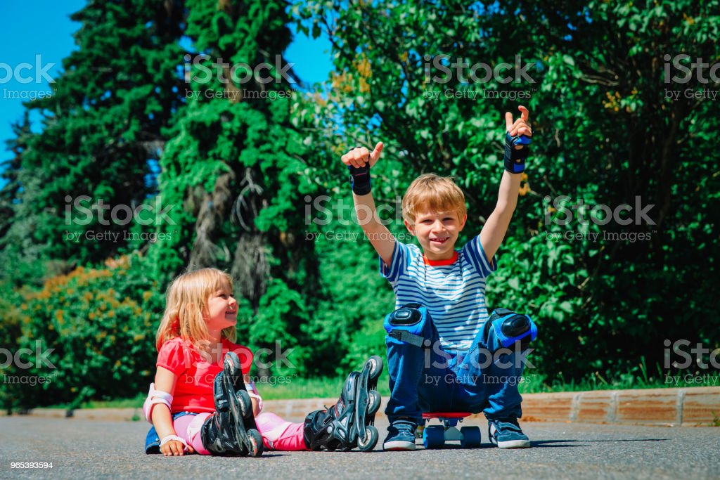 happy kids on roller skates and skateboard outside royalty-free stock photo
