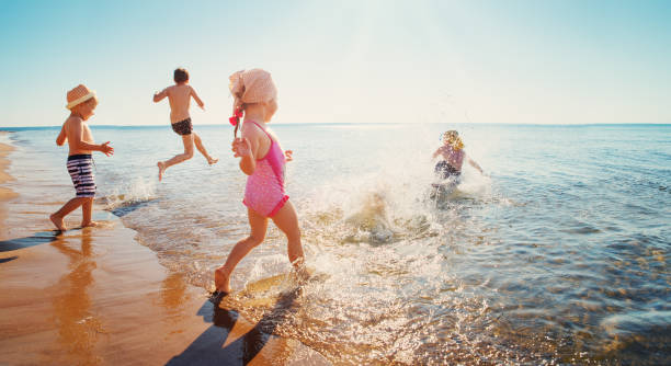 happy kids on vacations at seaside running in the water - nuoto mare foto e immagini stock