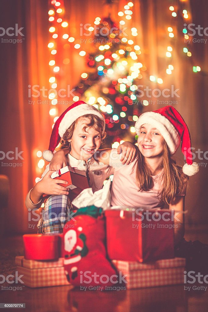Happy kids opening their Christmas presents zbiór zdjęć royalty-free