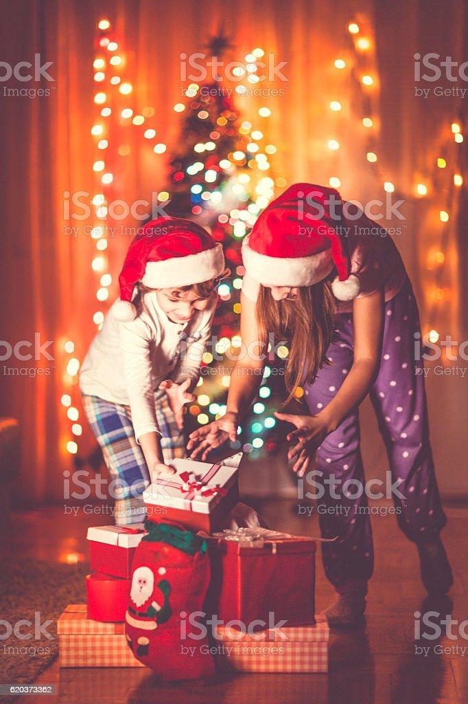 Happy kids opening their Christmas presents zbiór zdjęć royalty-free