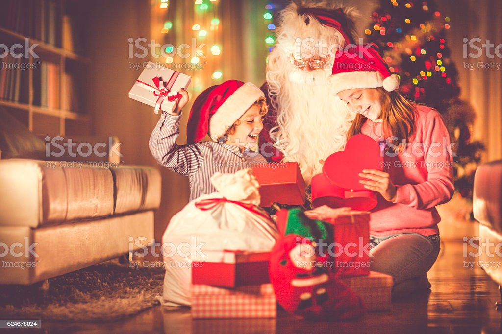 Happy kids opening their Christmas presents stock photo