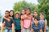 A diverse group of kids are standing in a park and posing for the camera. They are embracing each other with hugs and piggybacks.