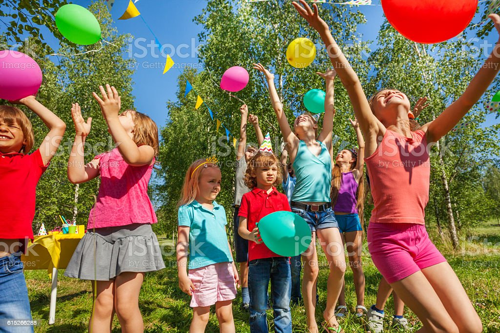 Happy kids playing and catching colorful balloons стоковое фото