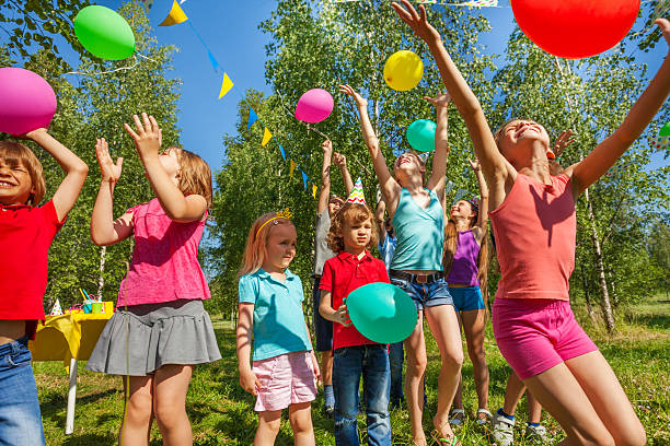 happy kids playing and catching colorful balloons - kinderparty spiele stock-fotos und bilder