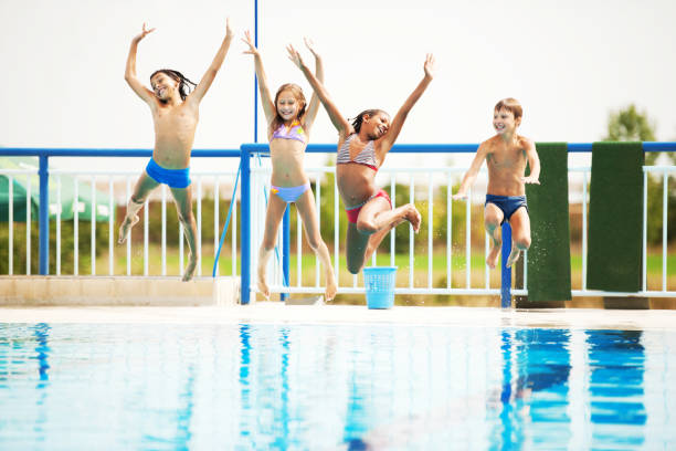 Happy kids playing and having fun together in the pool. stock photo