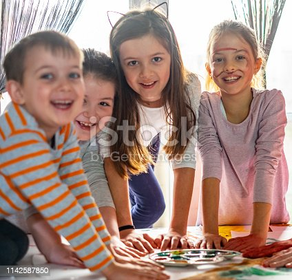 154371635 istock photo Happy kids playing and painting 1142587850