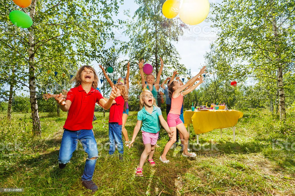 Happy kids playing balloons at summer park стоковое фото