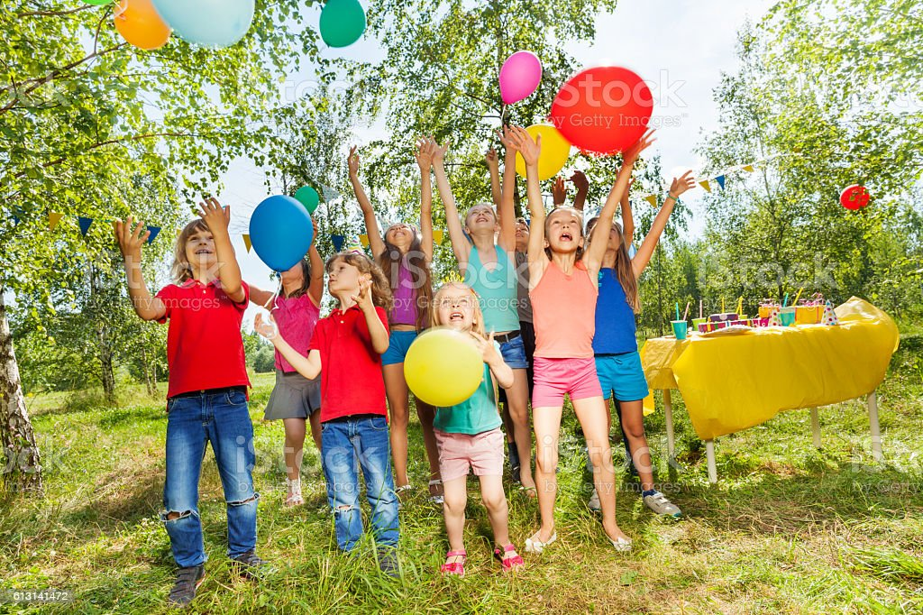 Happy kids playing colorful balloons outside стоковое фото