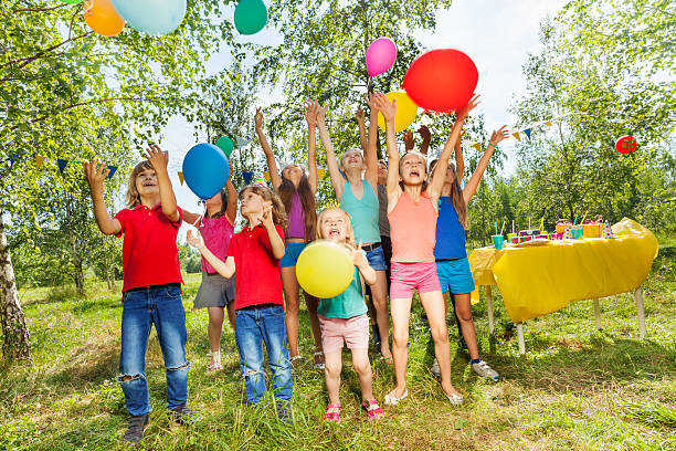 Cтоковое фото Happy kids playing colorful balloons outside