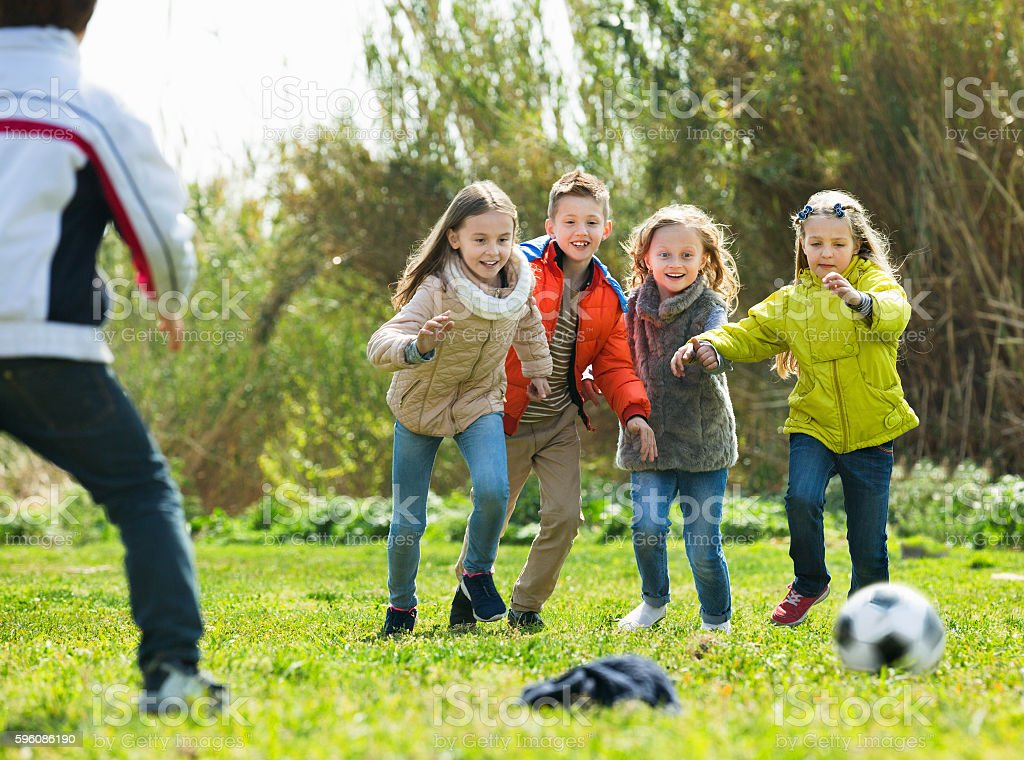Happy kids playing football outdoors royalty-free stock photo