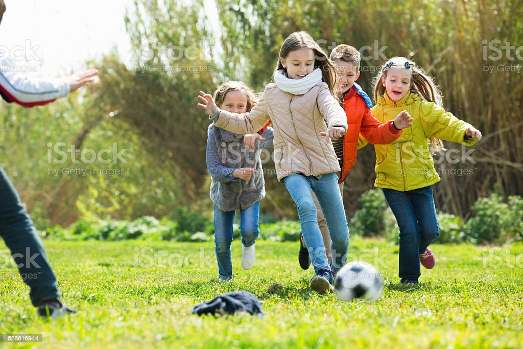Happy kids playing football outdoors stock photo