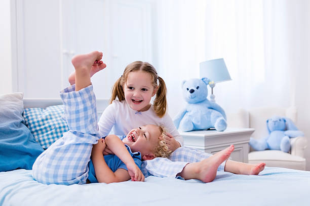 Happy kids playing in white bedroom stock photo