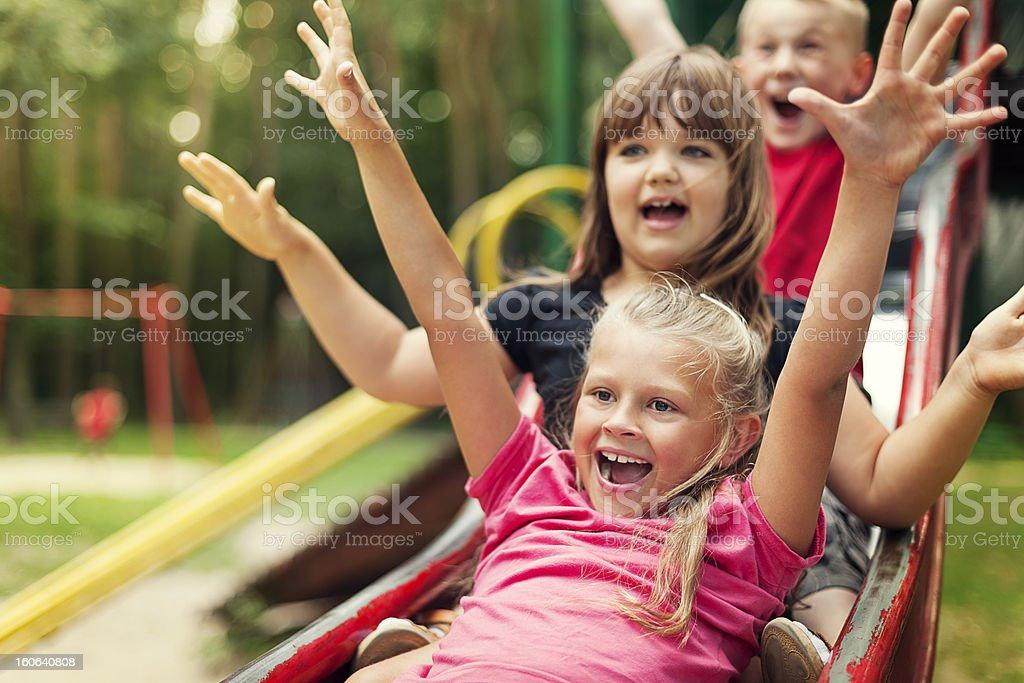 Happy kids playing on slide stock photo