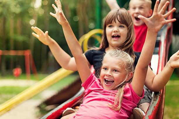 happy kids playing on slide - sliding stock photos and pictures