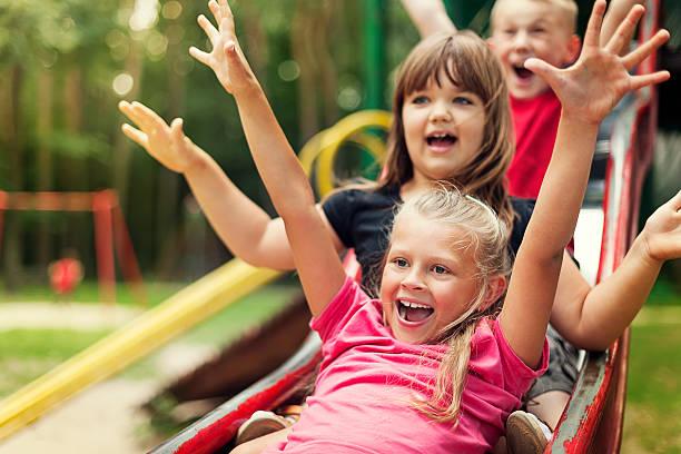 Happy kids playing on slide stock photo