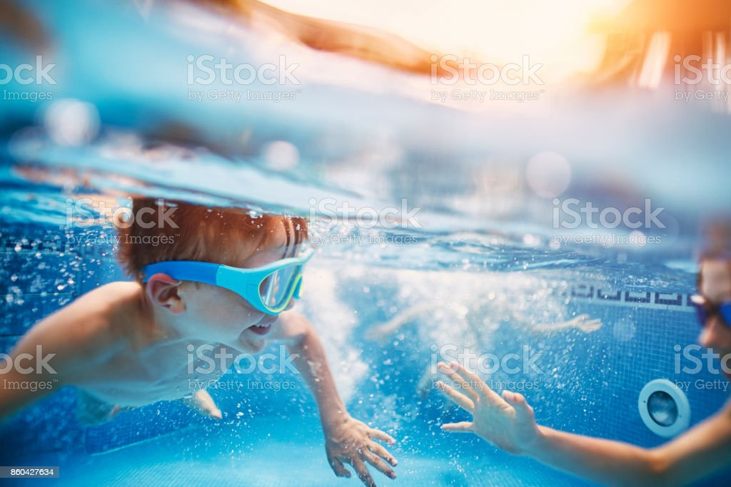 Happy kids playing tag underwater stock photo