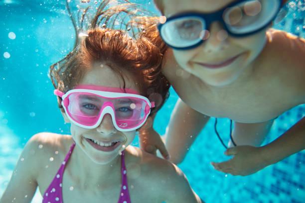 Happy kids playing underwater stock photo