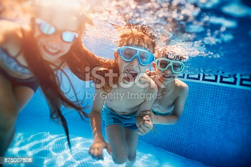 istock Happy kids playing underwater 875007808
