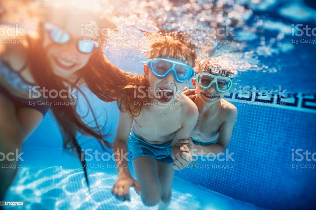 Happy kids playing underwater stock photo
