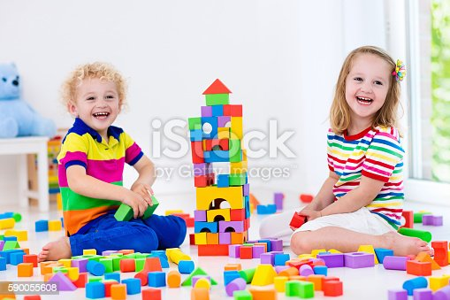 Kinder Garden: Happy Kids Playing With Colorful Toy Blocks Stock Photo